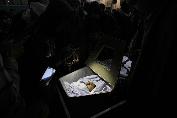 Omaiset surivat Baqir Ali Bangashin, 13, arkun äärellä tiistai-iltana.