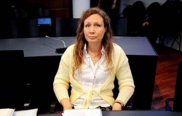 Anneli Auer katseli tyynesti toimittajia ja kuvaajia oikeusalissa.