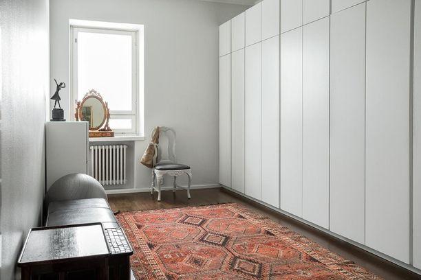 Kaipaatko selkeyttä ja järjestystä? Isot, tilavat kaapistot kätkevät sisäänsä rutkasti vaatteita, mutta ulospäin tila näyttää harmoniselta. Värikäs mattovalinta piristää vaatehuoneen ilmettä.