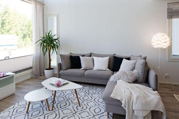 Tästä olohuoneesta löytyy jo monta skandinaavisen sisustuksen kulmakiveä: tuttu matto, harmaan ja valkoisen sävyt, puujalkaiset sohvapöydät ja mustaa tyynyjen muodossa.