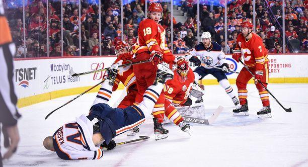 Calgary Flamesin Matthew Tkachuk (19) taklasi Edmonton Oilersin Zack Kassiania (44) päähän ottelun avauserässä. Tkachukin toisen erän törkytaklaus johti yksipuoliseen tappeluun.