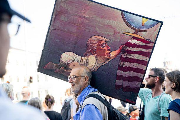 Andy Ruina kantoi Esplanadin puistossa mukanaan suurta taulua, jossa on kuvattuna Trump vauvana. Kuvassa Trump kiskoo Yhdysvaltojen lipun näköistä pöytäliinaa maapallon alta. Ruina kertoo, että taulu kuvastaa sitä, miten Trump kuvittelee auttavansa Amerikkaa, vaikka hän oikeasti vain tuhoaa maailman. Lopulta Trump hajottaa myös Yhdysvaltoja. Kuva on norjalaisen sarjakuvapiirtäjän Christian Bloomin kynästä.