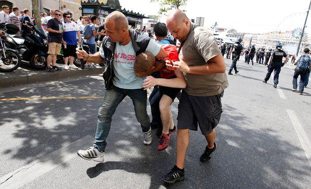 Siviiliasuiset poliisit taluttivat Englannin kannattajaa.