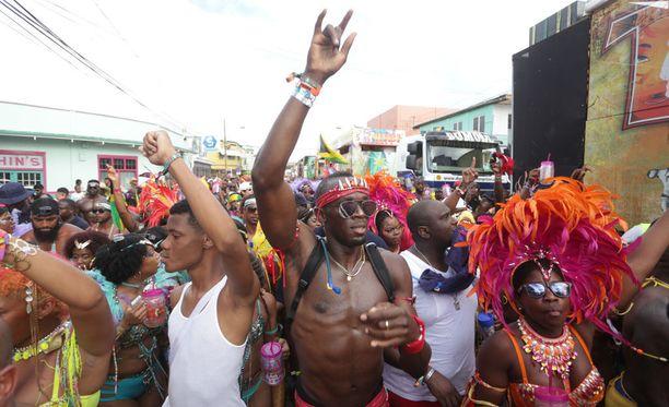 Usain Bolt (kuvassa keskellä) juhli pelti paljaana Trinidad ja Tobagon karnevaaleissa viime helmikuussa.
