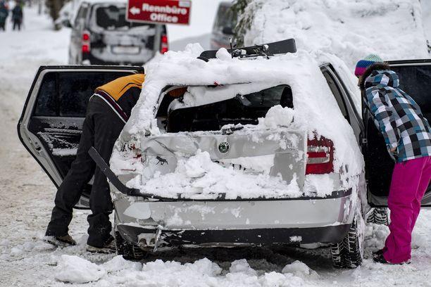 Ihmiset tutkivat lumivyöryn vahingoittamaa autoaan tiistaina Ramsaussa.