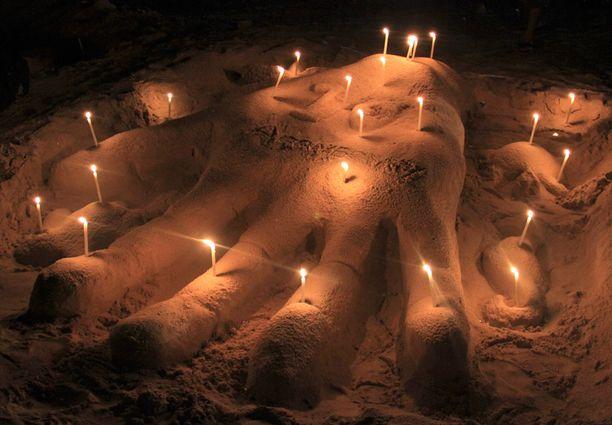 Phuketissa Patong-rannalle muodostettiin hiekasta käden kuva tsunamin uhrien muistoksi.