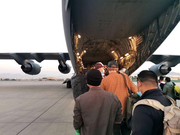 Suomen Afganistanista evakoimia afgaaneja nousemassa lentokoneeseen Kabulin kentällä.