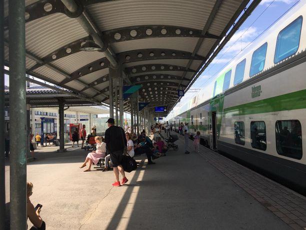 Vilvoittelevia ihmisiä Seinäjoen asemalaiturilla junan seisokin aikana.