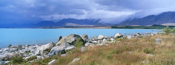 Turkoosinsininen Tekapo-järvi Uudessa-Seelannissa. Kirkas väri johtuu kalkkikivestä.