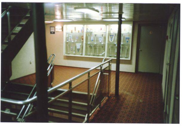 Rappukäytävä kannella kuusi. Seinän lasivitriinissä oli urheilupalkintoja.
