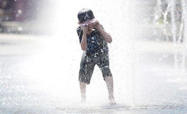 Pikkupoika vilvoittelee suihkulähteessä ennätyshelteiden piinaamassa Montrealissa.