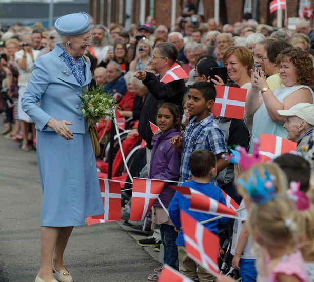 Paikalliset saapuivat tervehtimään laivalla paikalle saapunutta kuningatarta.
