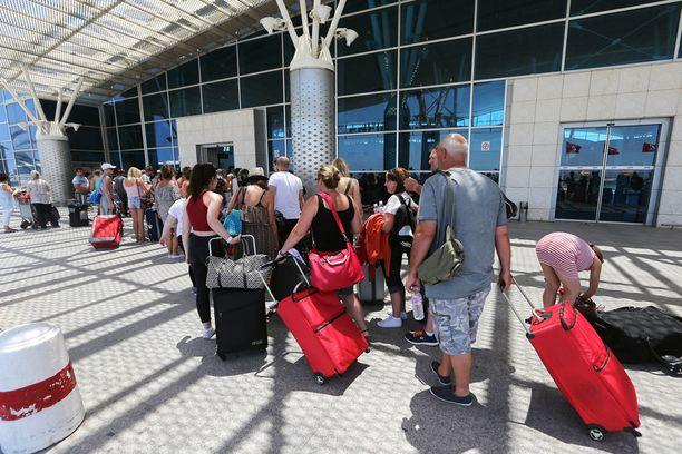 Brittituristit jonottivat lauantaina Enfidhan lentokentällä Soussessa. Tuhannet turistit ovat poistuneet Tunisiasta perjantain iskun pelästyttäminä.