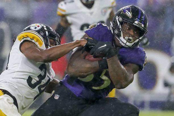 Gus Edwards taistelemassa divisioonavastustaja Pittsburgh Steelersiä vastaan.