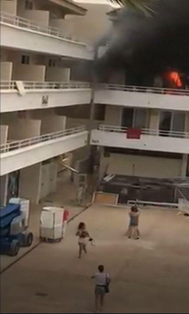 Turistit pakenivat palavasta hotellista.
