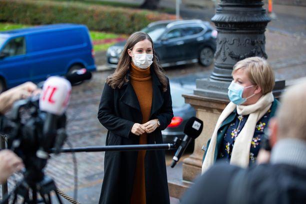Annika Saarikko antaa haastattelua Säätytalolla 23. lokakuuta, Sanna Marin odottaa vuoroaan.