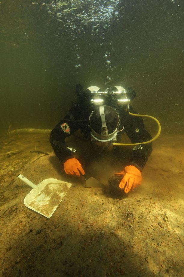 Eveliina Salo kaivaa vedenalaista liettä esiin pohjasta.