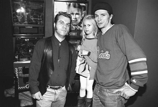"""Kuva vuodelta 1996. Kuvassa Melrosen rumpali Rami sekä Mika """"Tokela"""" Tuokkola Milla-tyttärensä kanssa."""