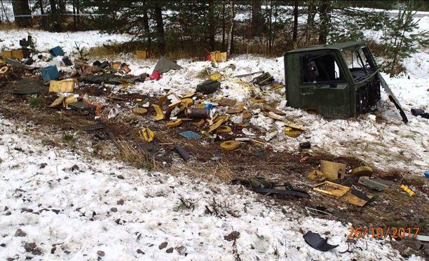 Kuvassa irronnut maastokuorma-auton hytti sekä tavaratilasta levinnyttä materiaalia.