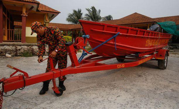 Malesialainen pelastushenkilökuntaan kuuluva mies valmistelee pelastusvenettä, jolla etsitään turmassa kadonneita.