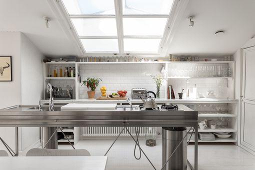 Helsingin kantakaupungissa sijaitsevan asunnon keittiöön valo tulvii kattoikunnasta.