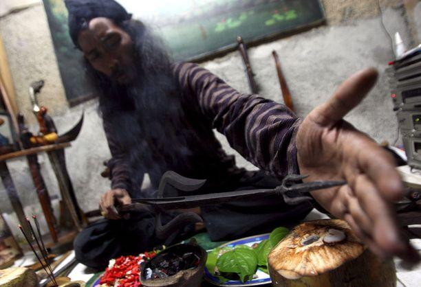 Indonesialainen shamaani suorittamassa puhdistusrituaalia Jakartassa vuonna 2008. Kuvituskuva.
