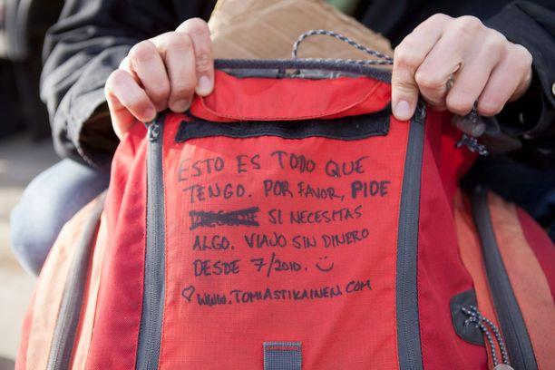 """Maailmanmatkaajan rinkan etuläpässä lukee espanjaksi: """"Tässä on kaikki, mitä omistan. Voisitko ystävällisesti pyytää, jos tarvitset jotain. Matkustan ilman rahaa 7/2010 lähtien."""""""