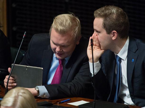 Keskustan eduskuntaryhmän puheenjohtaja Antti Kurvinen ja keskustan varapuheenjohtaja Petri Honkonen keskinäisessä neuvonpidossa eduskunnan istuntosalissa.