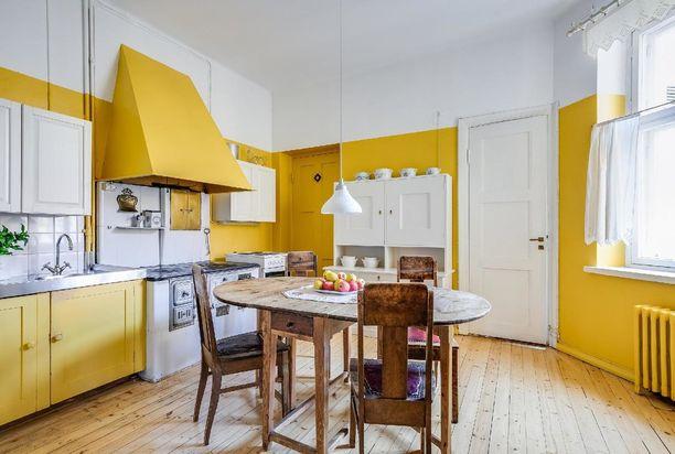 Maalaishenkisessä keittiössä seinät ja osa kaapeista ovat keltaisia. Aurinkoinen ja lämmin tunnelma välittyy.