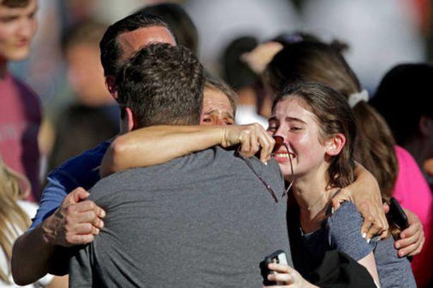 Floridan Parklandissa tapahtuneessa kouluammuskelussa kuoli 17 ihmistä. Kuvassa järkyttyneet ihmiset halaavat ja lohduttavat toisiaan.