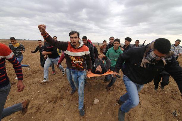 Palestiinalaiset evakuoivat yhteenotoissa loukkaantunutta mielenosoittajaa Gazassa.