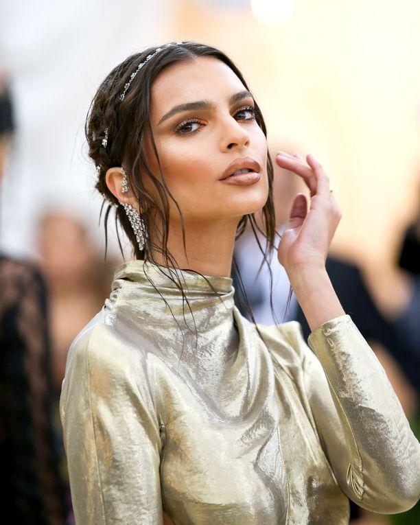 Hiuskorut, korvikset, wet look -kampaus, kuparinhohtoinen meikki - Emily Ratajkowskin look on kuin jumalattarella.