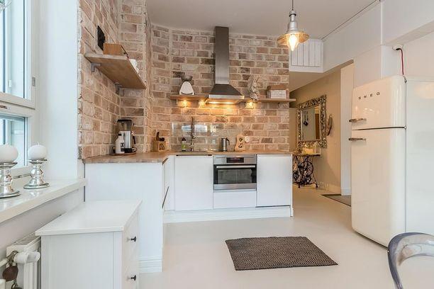 Rustiikkinen tiiliseinä on keittiön katseenkiinnittäjä. Lieden takaa seinä on suojattu roiskeilta.