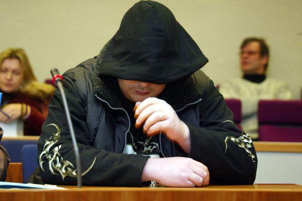 Paloittelumurhasta syytetty Janne Hyvönen peitteli kasvojaan hovioikeudessa.