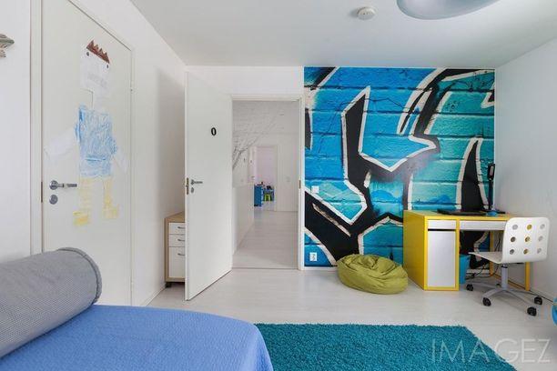Taiteellinen koululainen ihastuu varmasti graffitihenkiseen seinään. Maton ja muut tekstiilit voi sävyttää tyylikkäästi seinän sävyihin.