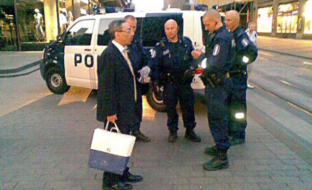 Eduskunnan puhemies Ben Zyskowicz (kok) selvittelemässä päällekarkausta poliisien kanssa Helsingin keskustassa.