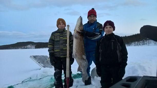 Laitilan perheessä kalastus on tullut läheiseksi harrastukseksi niin vanhemmille kuin lapsillekin. Kuvassa isä ja pojat jäällä hurjan kokoisen hauen kanssa verkkojen kokemisen jälkeen.