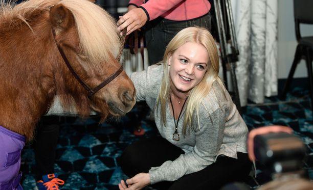 """Emilia Bottas poseerasi Helsinki Horse Show'n tiedotustilaisuudessa hieman omaansa pienemmän """"kulkupelin"""" rinnalla."""