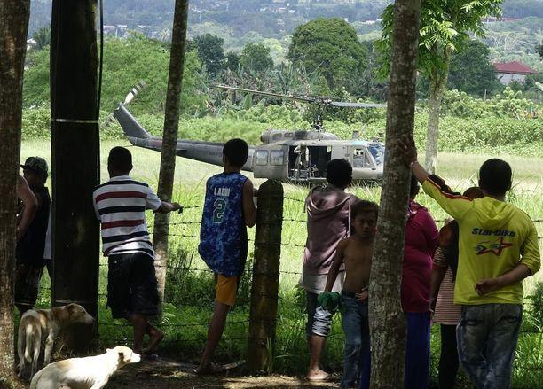 Mindanaon saarella eläviä kyläläisiä katselemassa Filippiinien armeijan helikoptereita.