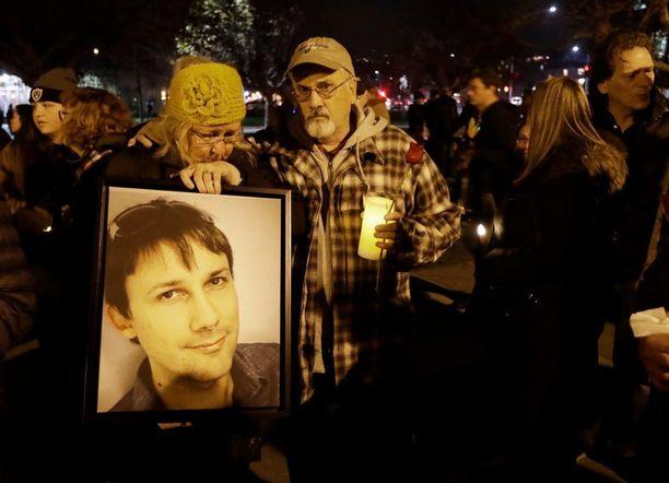 Judy Hough (vas.) ja hänen miehensä Brian pitelivät tulipalossa menehtyneen poikansa Travisin valokuvaa Lake Merrittissä järjestetyssä muistotilaisuudessa.