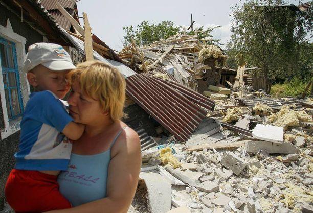 Nainen ja lapsi talon raunioilla Donetskin kaupungin lähettyvillä Itä-Ukrainassa 18. kesäkuuta.