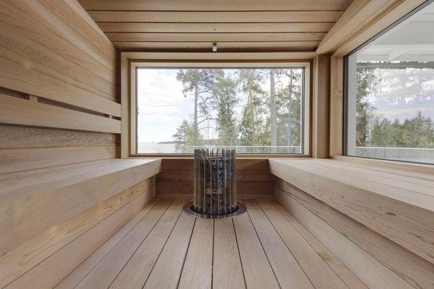 Tässä selkeälijaisessa modernissa saunassa on kaksi suurta ikkunaa, joista on maisemat merelle.