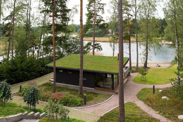 Viherkattoinen rantasauna maastoutuu tyylikkäästi omakotitalon pihapiiriin Espoon Suvisaaristossa.