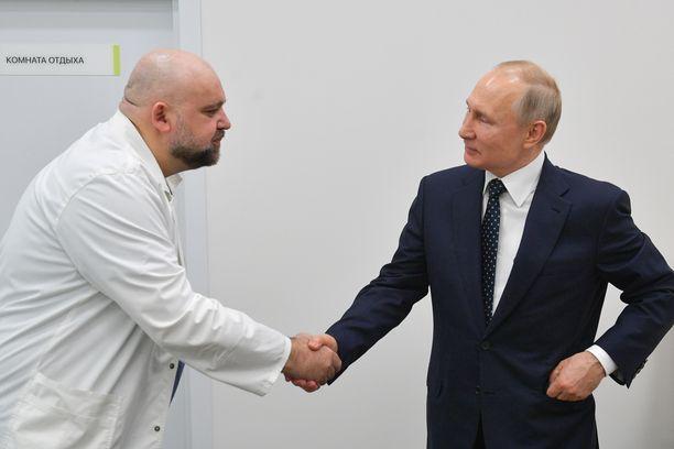 Putin (oik.) kuvattiin kättelemässä vastuulääkäri Denis Protsenkoa (vas.)
