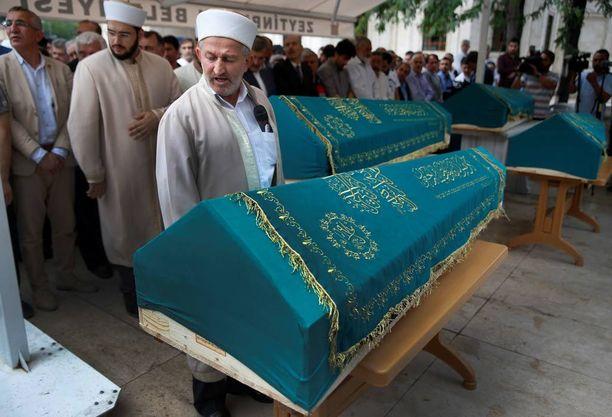 Imaami Amirin perheen arkkujen äärellä torstaina. Amirin perheestä neljä kuoli Istanbulin Ataturkin lentokentälle tehdyssä iskussa tiistaina.