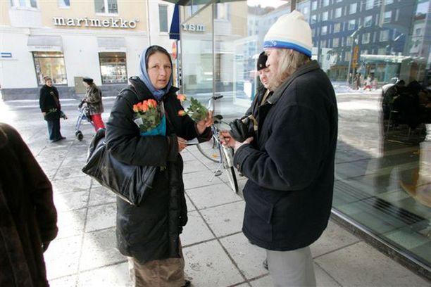 Nainen kauppasi ruusuja pankin edessä kävelykatu Rotuaarin päässä.
