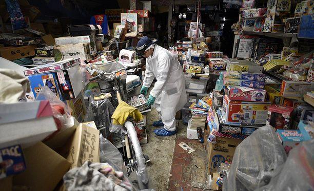 Namiessa lelukauppaa pitänyt Yuzo Mihara tutkii liikkeensä varastoja. Kaikki oli jätettävä kun kaupunki evakuoitiin.
