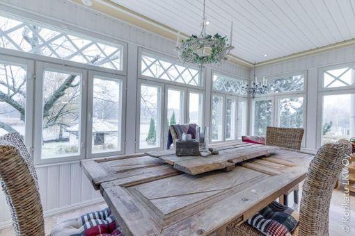 Kun lasikuisti on riittävän iso, sinne voi sijoittaa vaikka ruokailupöydän. Rottinkituolit ja vanha pöytä sopivat tunnelmaan.
