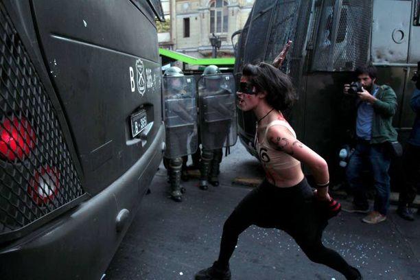 Nuori nainen hakkasi poliisiautoa Chilen pääkaupungissa Santiagossa.