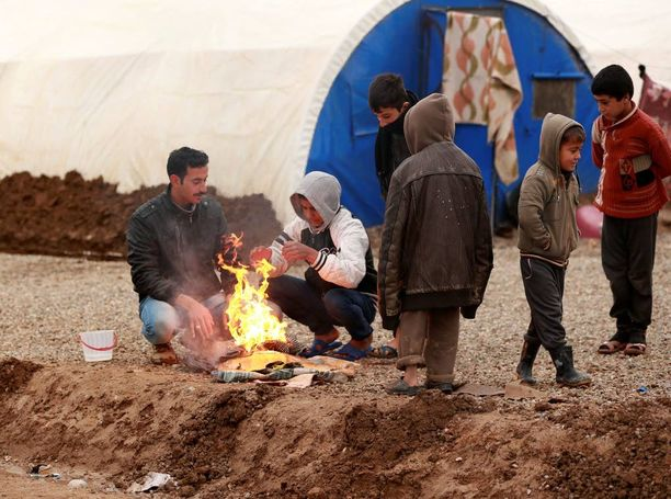 Lapset ja aikuiset lämmittelivät avotulen ääressä Khazirin leirillä.